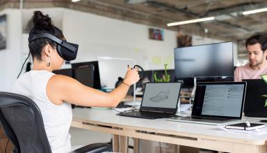 Mulher sentada no computador com óculos de realidade aumentada