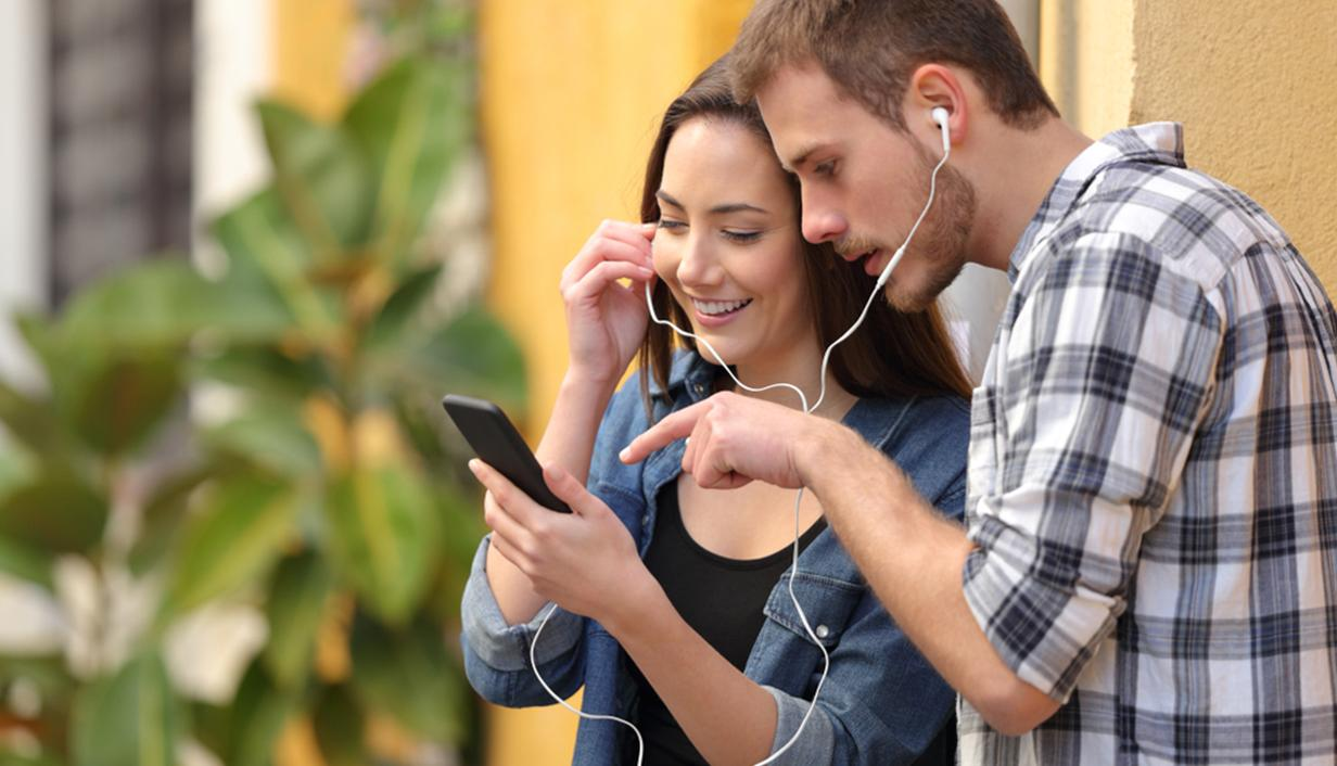 Couple sharing earphones and looking at mobile phone