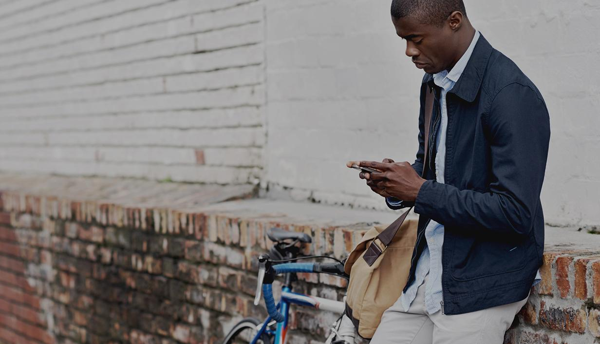 Man with bike on mobile phone