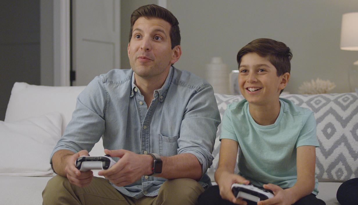 A father and son sitting on a sofa and playing a video game.