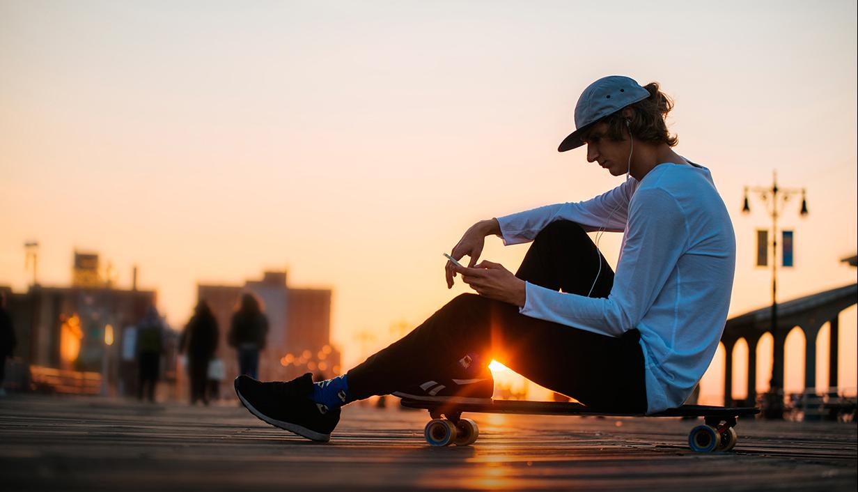 Skateboarder listening to his mobile phone via headphones