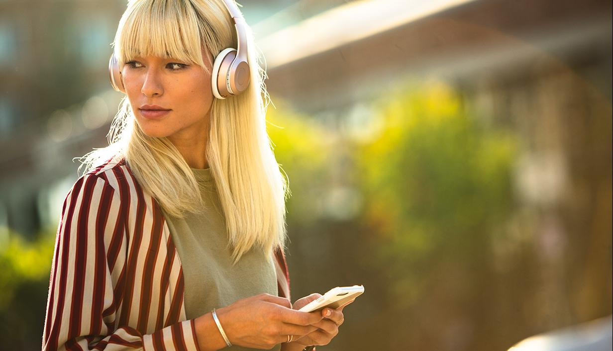 Woman listening to headphones with her mobile phone