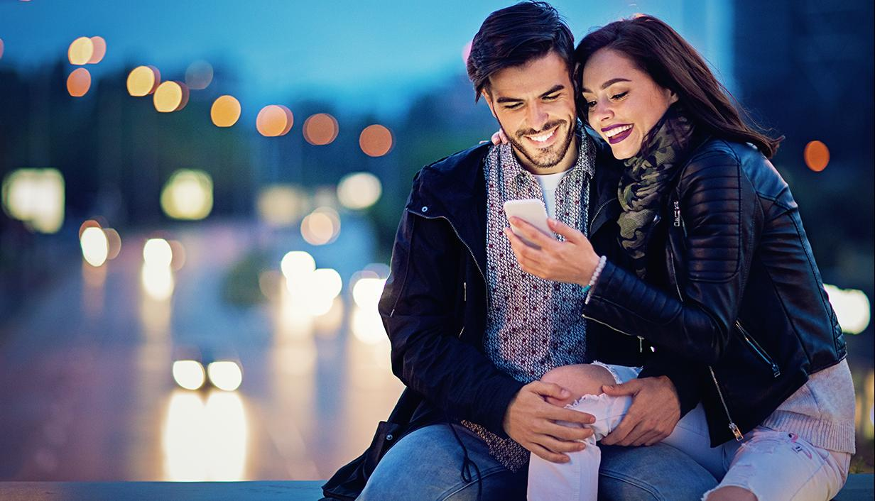 Couple on bridge looking at phone