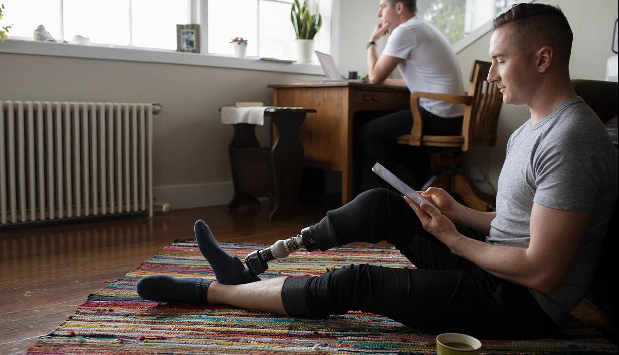 Man with prosthetic limb sitting on a colorful rug using a tablet mobile device