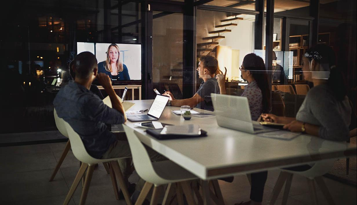 People at a conference table video chatting with their colleague
