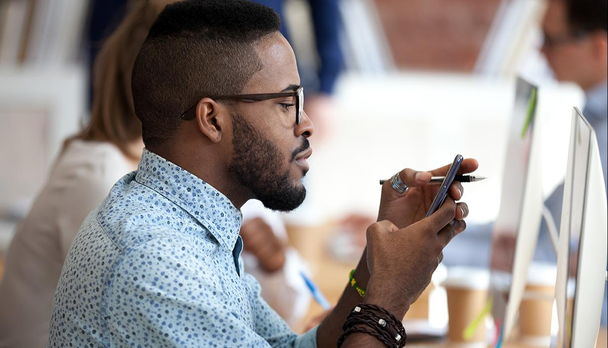 Business man looking at mobile phone while working