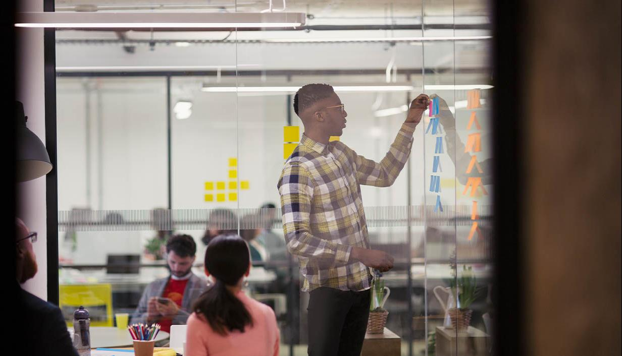 A man reviews post-it notes on a glass wall.