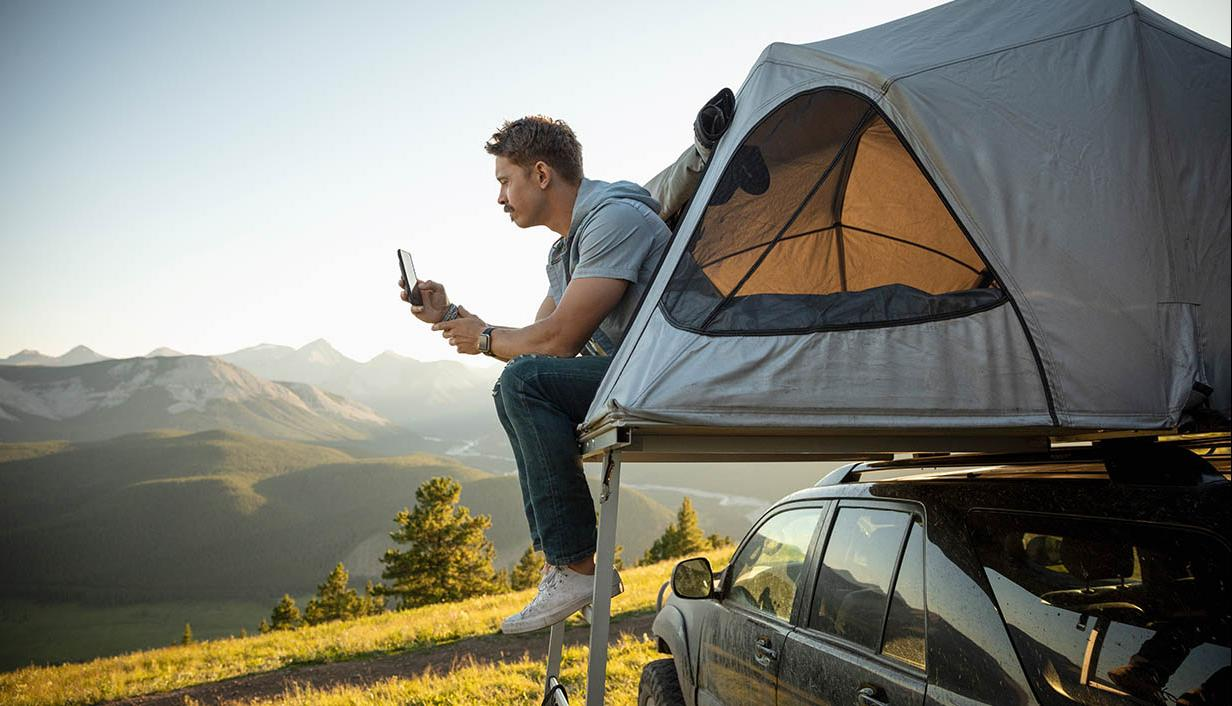 Man camping looks at his phone from the tent.