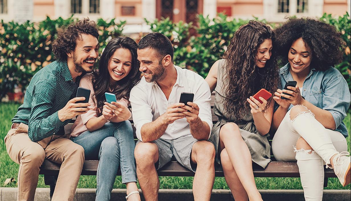 Group of friends on bench interacting with mobile phones
