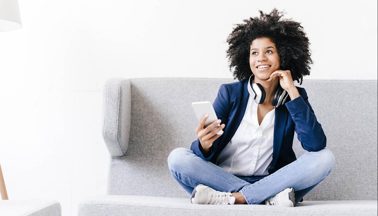 woman cross legged with phone and headphones