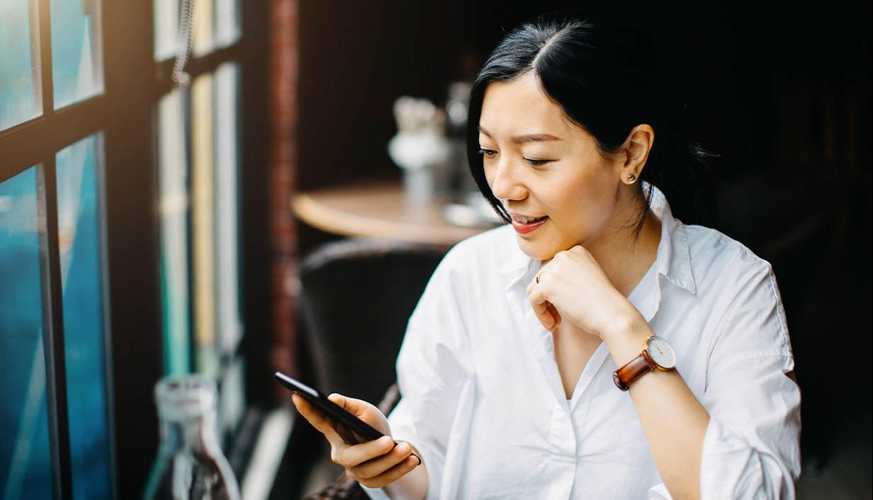 woman smile at phone in cafe