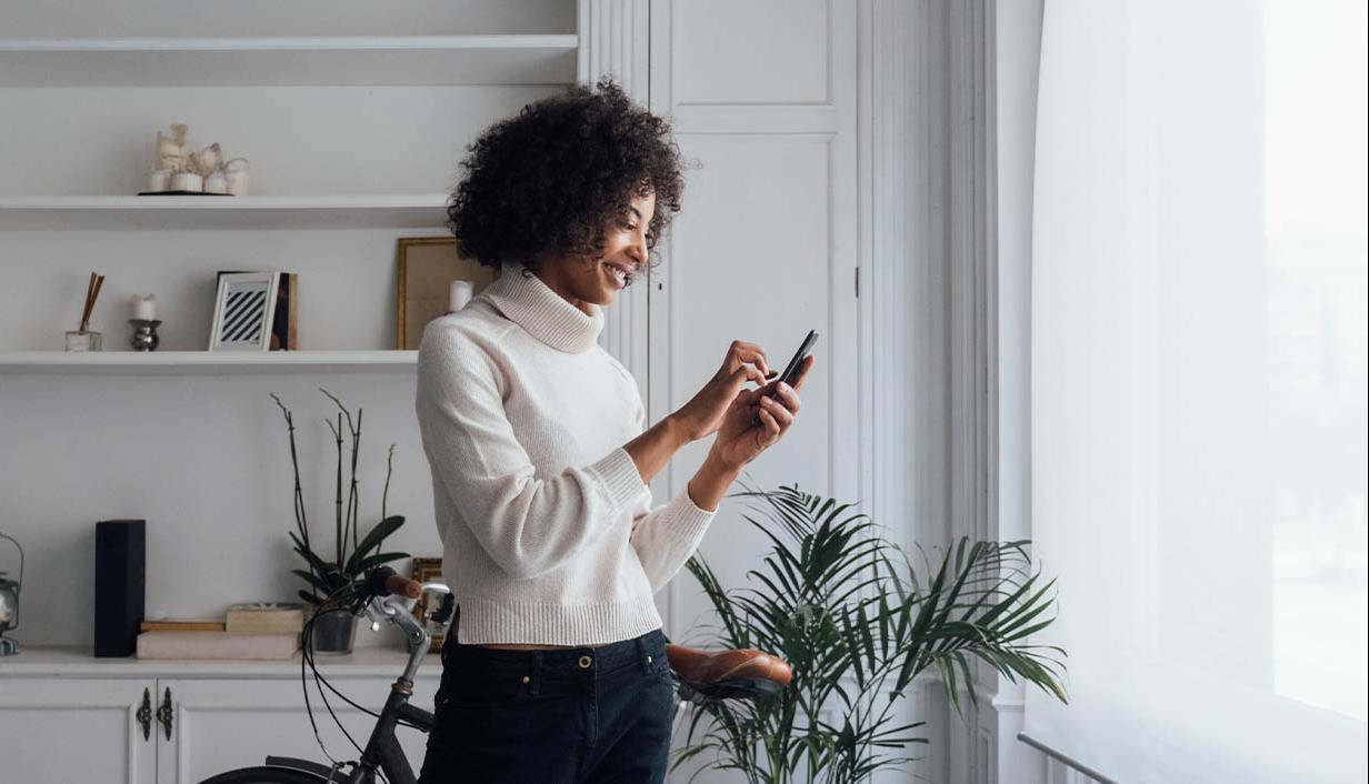 woman with white sweater typing on phone