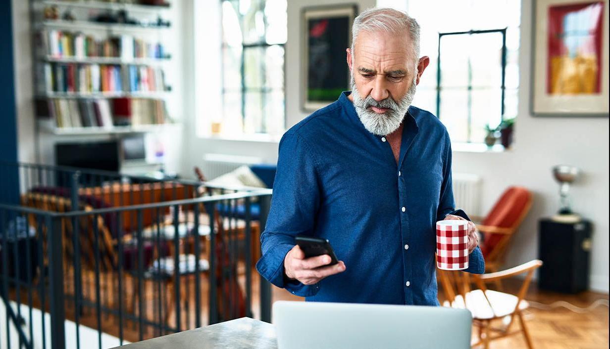 Bearded man in kitchen watching a webinar on his laptop