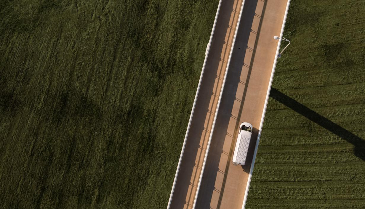 Car driving on road next to fields