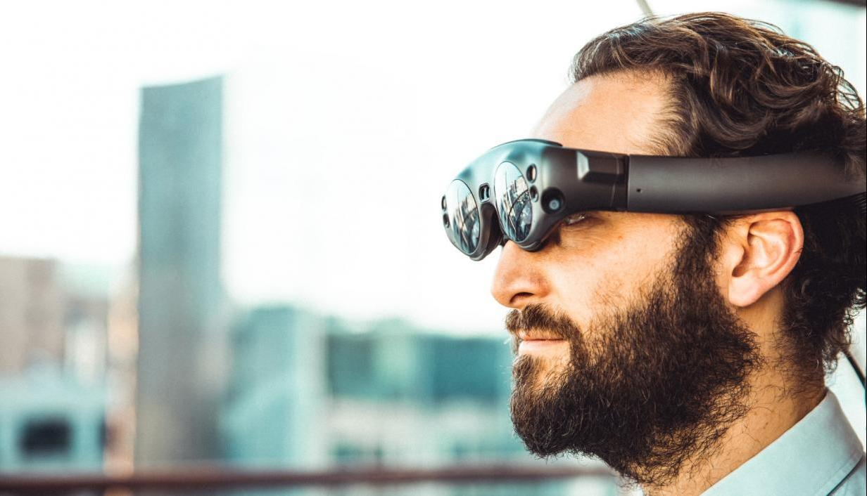 man with beard wearing VR goggles in front of city landscape