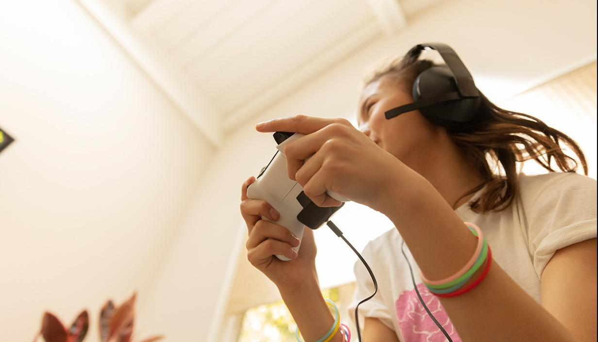 Girl playing on console with controller with headseet