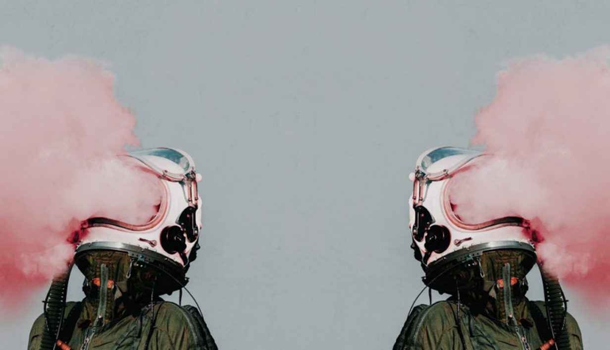 Mirrored image of persons wearing motorcycle helmets and red smoke pouring out