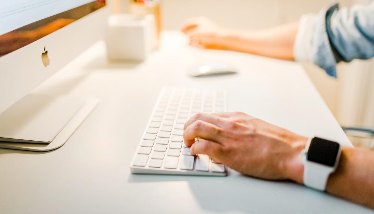 Man at keyboard on Mac computer