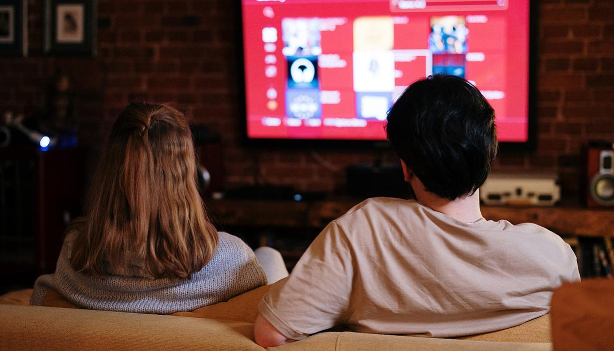casal de costas em um sofa assistindo televisão
