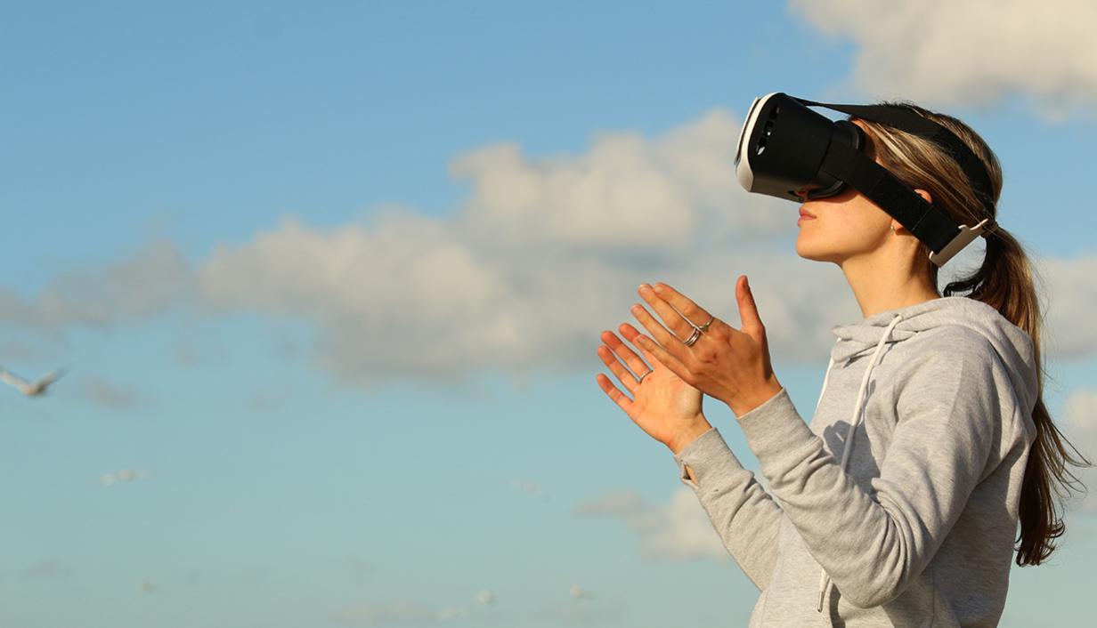 mulher usando um casaco cinza, com óculos de VR e no fundo o céu azul com nuvens