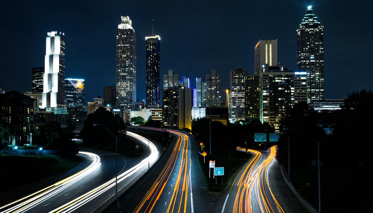 imagem de cidade anoitecendo com carros passando em grandes avenidas