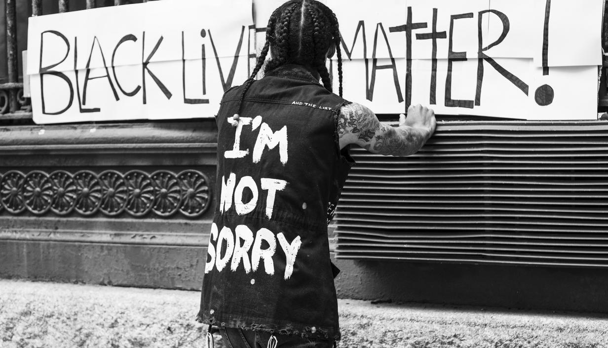 foto preto e brando de um home de costas pendurando um cartaz do BLM