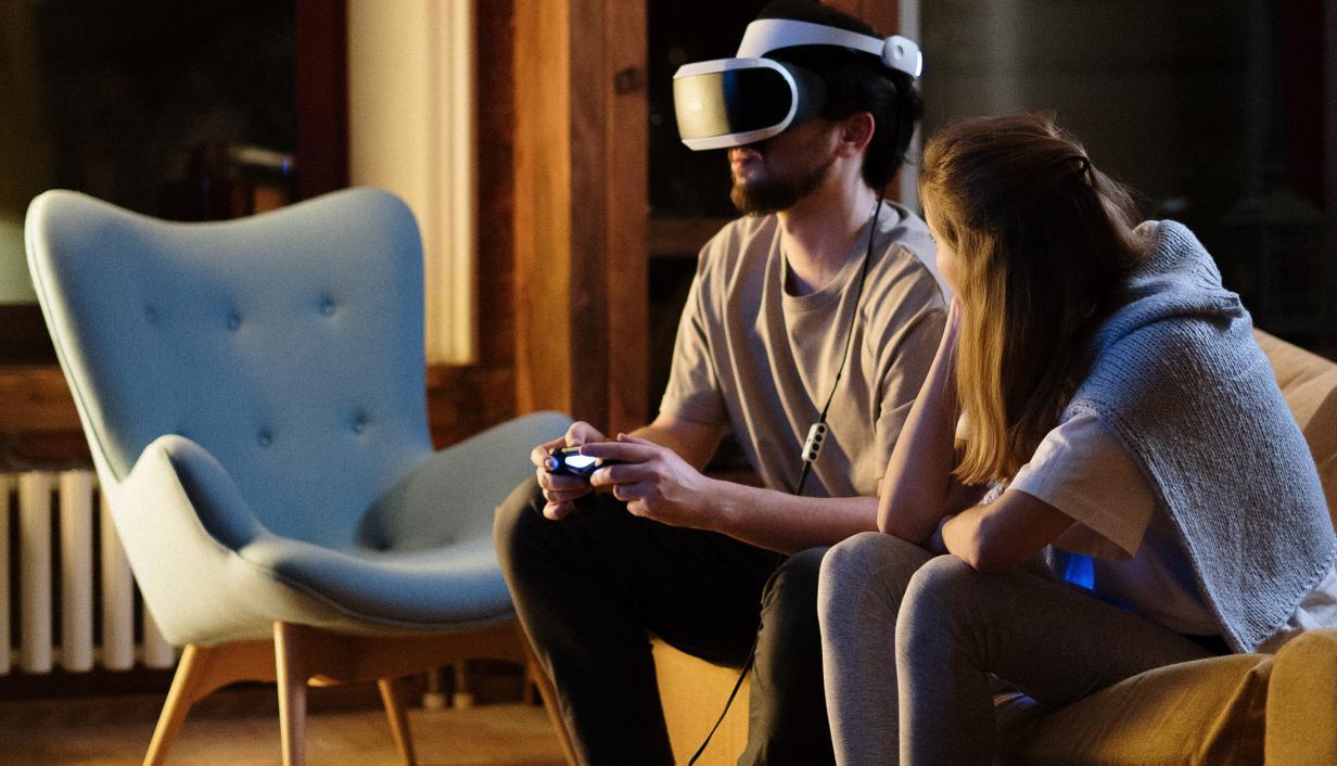 casal em sala de estar testando oculos de realidade virtual