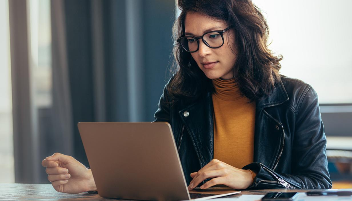 Woman wearing glasses looking at laptop
