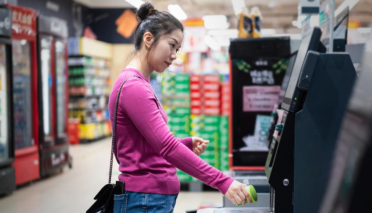 Woman at grocery store self check-out