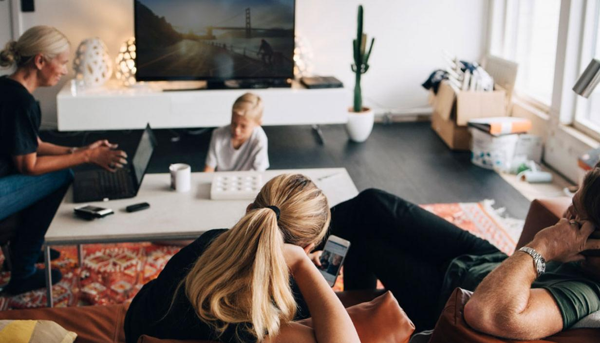 Family in living room watching TV and on devices