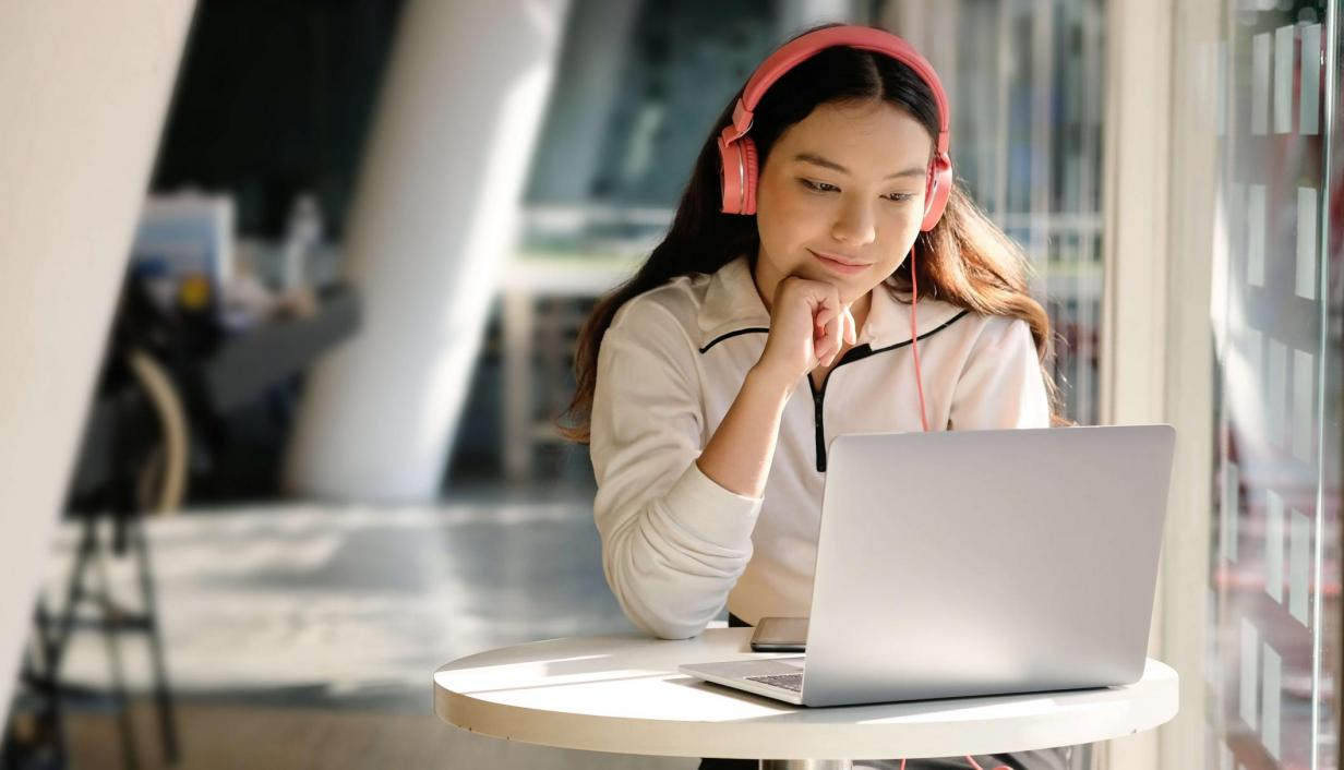 Woman staring at her laptop deep in thought with a happy smirk.