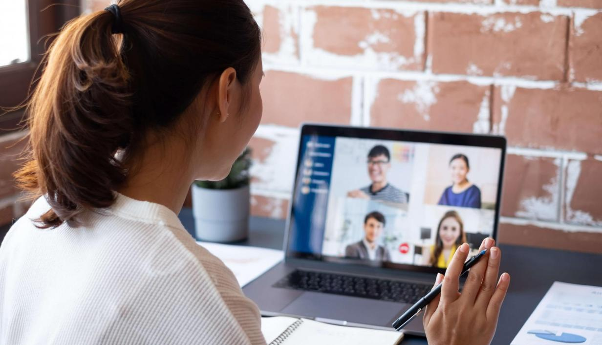 Woman holds pen in hand, looks at laptop, while on video call with four people.