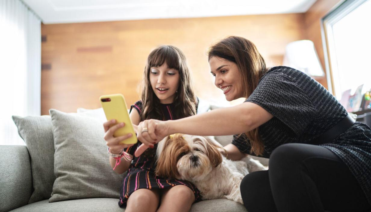 A young girl and woman, sitting on a sofa with a small dog, look at a mobile device together