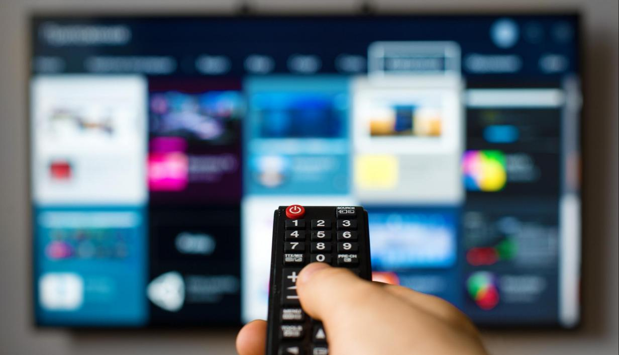 A hand holding a remote control pointing at a TV.