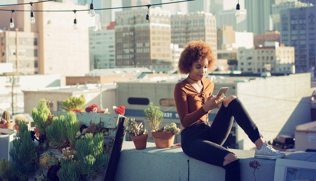 A woman on a building rooftop looking at her mobile device.